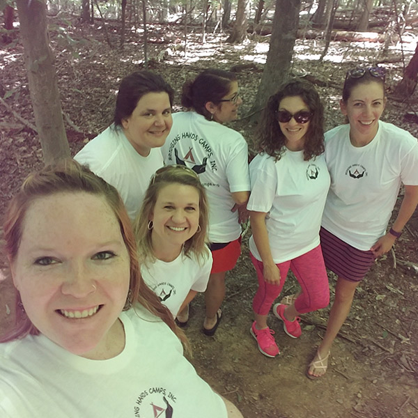 group picture of people in white tshirts in woods